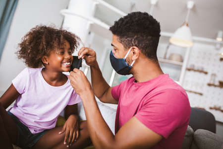 Father in a medical mask puts a protective mask on his daughter at home.Kid safety after coronavirus pandemic.