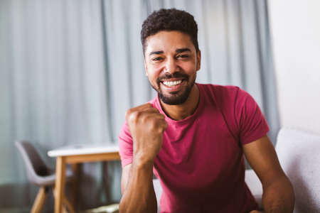 Portrait of smiling african american man, arm fists pumped celebrating success.