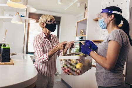 Courier delivering shopping to senior woman with face mask, corona virus and quarantine concept.