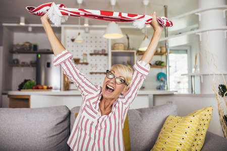 Elderly woman emotionally watching soccer on tv and celebrating victory at home. 写真素材