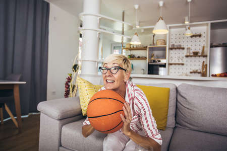 Elderly woman emotionally watching basketball on tv and celebrating victory at home. 写真素材