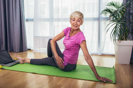 Happy senior woman doing stretching exercises in front of laptop at home, watching online tutorials