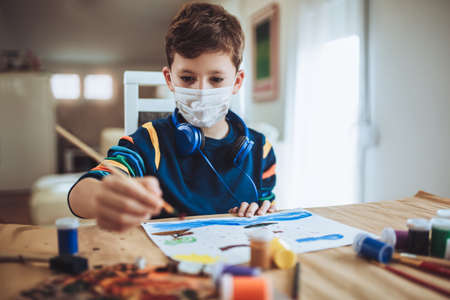 Cute little boy painting a picture in home studio