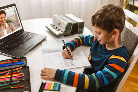 Little boy writes musical notes and violin key at home online course on laptop.Online training, online classes.