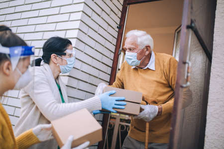 Young female volunteers in mask gives an elderly man boxes with food near his house. Quarantined, isolated. Coronavirus covid-19. Donation