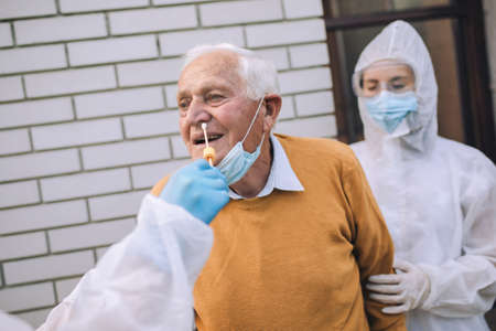 Doctors in a protective suit taking swab from a senior man to test for possible coronavirus infection. Taking corona virus test sample at home concept, senior man in quarantine. Stock Photo