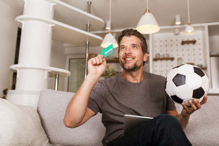 Young soccer fan man watching football game on television at living room couch. He holds a credit card and a digital tablet for online betting.