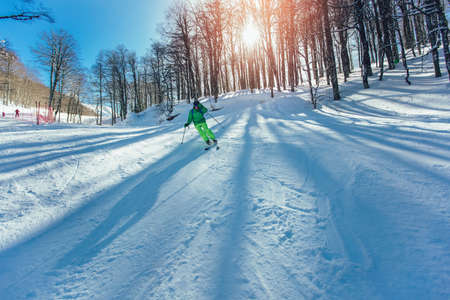 Skier in mountains. Professional skier athlete skiing of ski resort.Winter vacation and sport concept.
