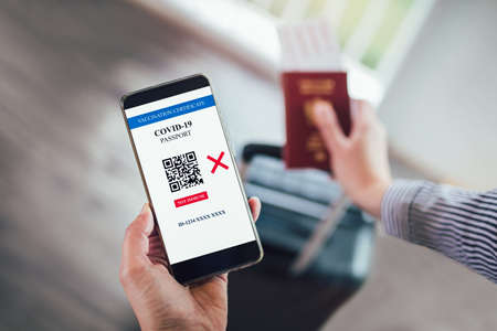 Vaccination, disease immunity passport, health and surveillance concepts. Smartphone displaying a not imunne digital vaccination certificate for COVID-19.