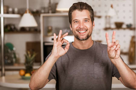 Young man showing gesture in sign language Stock Photo