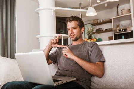 Young man showing gesture in sign language using laptop, make video call. Stock Photo