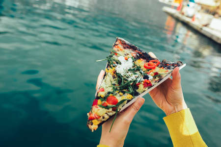 Woman's hand holding italian pizza with black dough and vegetables. Sea background.