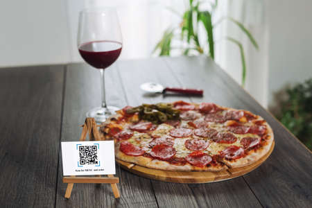 Scan to get discounts or order for pizza. The concept of using a phone to transfer money or paying money online without cash.FAKE QR.QR codes/barcodes in the image not contain offensive language, brand names, or links to websites or products.