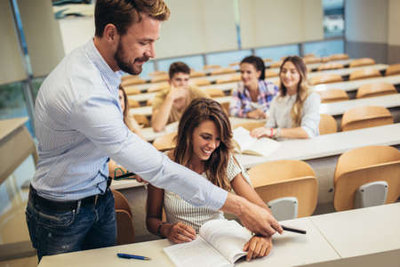 Male tutor teaching university students in classroom.