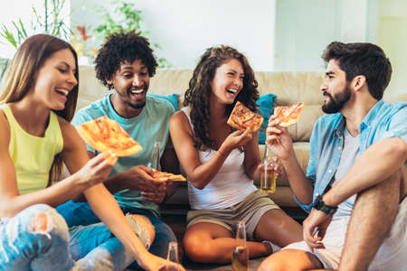 Group of young friends eating pizza.Home party. Banco de Imagens