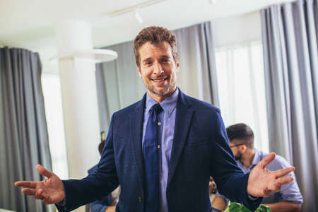Businessman leader looking at camera in modern office with businesspeople working at the background. Teamwork concept.