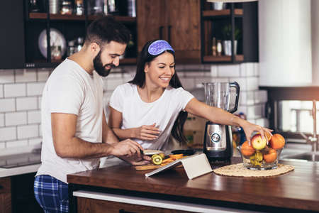 Portrait of a young loving couple making breakfast at home.