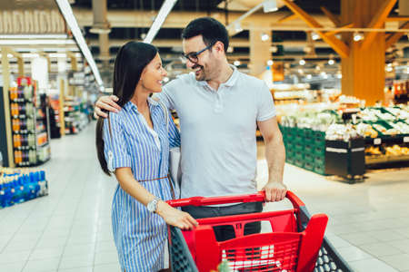 Happy young couple smiling while walking in food store with shopping cart Banque d'images