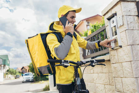 Male courier with bicycle delivering packages using smartphone