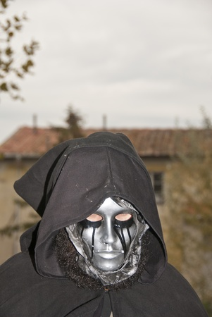 Masked Woman wih Hood against cloudy Sky, Italy photo