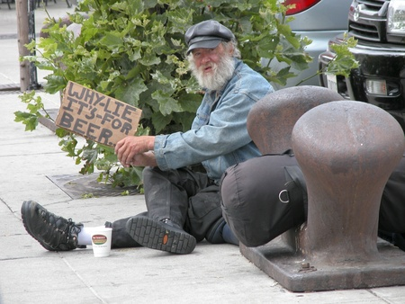 SAN FRANCISCO, U.S.A. - AUGUST 27: Unidentified tramp with a sign begs to buy Beer on August 27,2003 in Fishermans Wharf, San Francisco, U.S.A. It is common in these streets to find a tramp but this one is a really playful