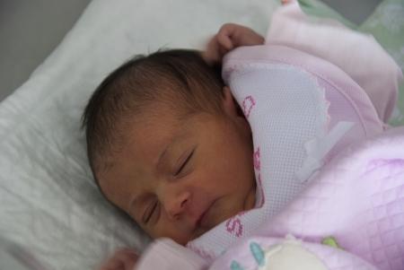 newborn baby girl: Newborn Baby Girl relaxing inside her Bed Stock Photo