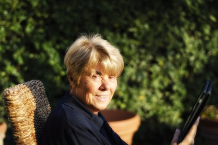 Retired Woman Relaxing Outdoor with her Tablet, Italy photo