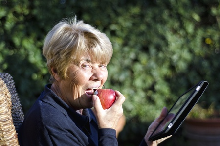 Retired Woman Eating Apple Outdoor with her Tablet photo