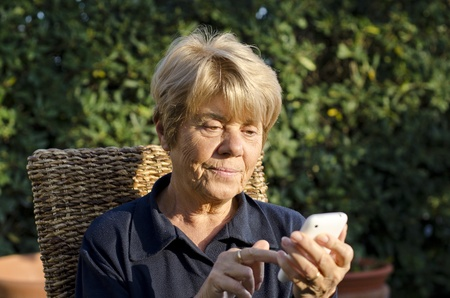 Retired Woman relaxing outdoor with her Smartphone, Italy