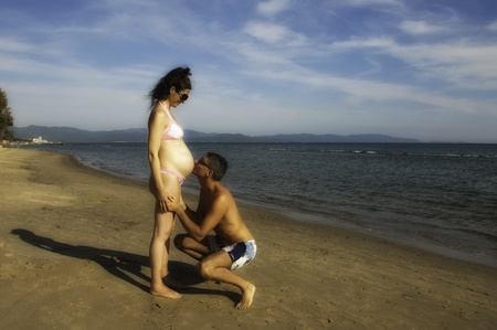 Pregnant Woman relaxing at the Beach with her Husband in Italy photo