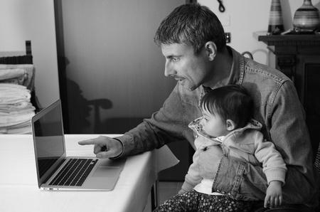 Man Teaching his Daughter Using Laptop, Italy photo