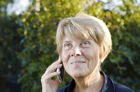 Senior Woman Speaking at the Phone Outdoor, Italy photo