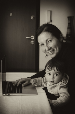 Mother using Laptop with her Daughter, Italy photo
