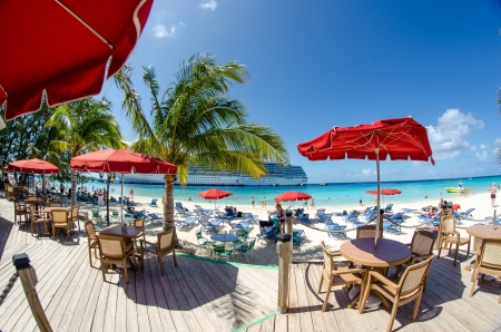 GRAND TURK, TURKS AND CAICOS - FEB 25: People relax on the beach with red umbrellas and turquoise water, February 25th, 2011 in Grand Turk, Turks and Caicos Stock Photo - 14682561