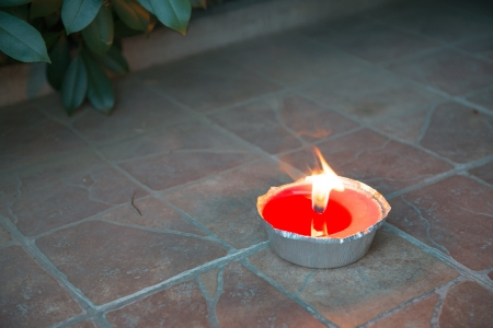 Lit Citronella candle isolated on a outdoor floor - Tuscany photo