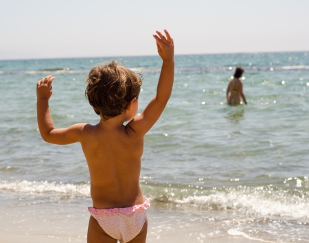 Cute baby playing with stone on tropical beach - Italy photo