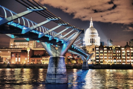 St. Pauls Cathedral and the Millennium Bridge at night in London, England photo