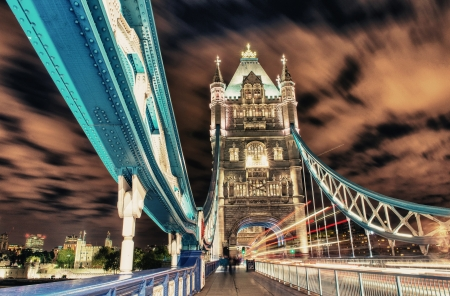 Tower Bridge in London, UK at night with traffic and moving red double-decker bus leaving light traces  Stock Photo - 15660336