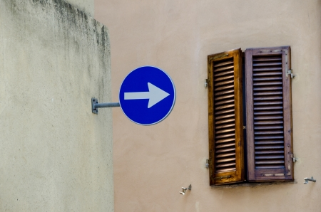 one lane street sign: One way sign with old window in Italy Stock Photo