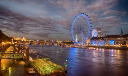 London skyline across the Thames from Westminster Bridge with blurred London Eye at night - UK