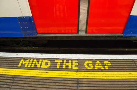 red tube: Cuidado con la brecha, advirtiendo en el metro de Londres - Reino Unido Editorial