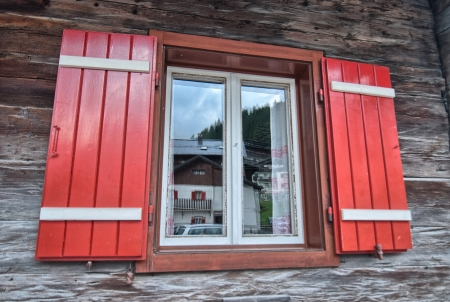 Typical red window of a wooden house, dolomites mountains. Stock Photo
