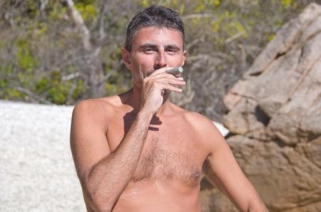 Man pretending to Smoke a Coral on a Beach, Australia photo