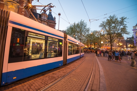 kilometres: AMSTERDAM - APR 30: Tram running in the city centre amongst pedestrians, April 30, 2013 in Amsterdam. The tram network comprises 16 lines and covers 213 kilometres Editorial