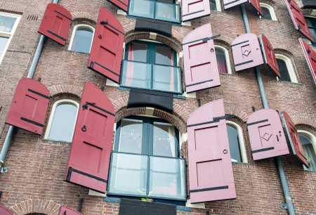 Amsterdam, Netherlands. Facade of a traditional house with beautiful red windows.