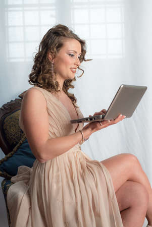 netbook: Beautiful young woman working with her netbook inside her bedroom