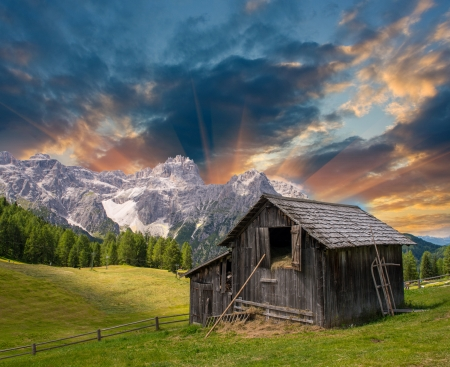 ranches: Shack on a mountain meadow - Sunset with fields and peaks. Stock Photo