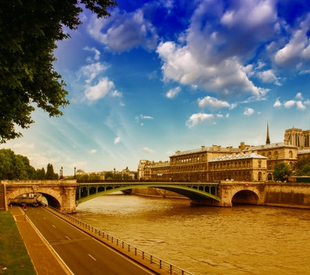 Sunset over Notre Dame Bridge in Paris with Seine river.