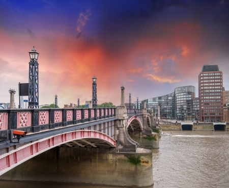 Lambeth Bridge, London. Beautiful red color and surrounding buildings at sunset. photo