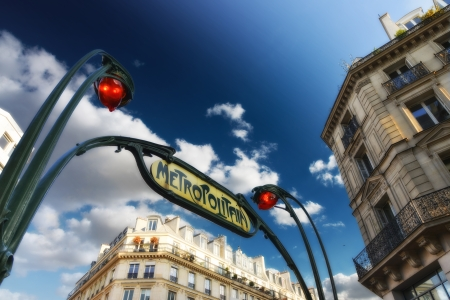 Metro station sign in Paris with beautiful sky.